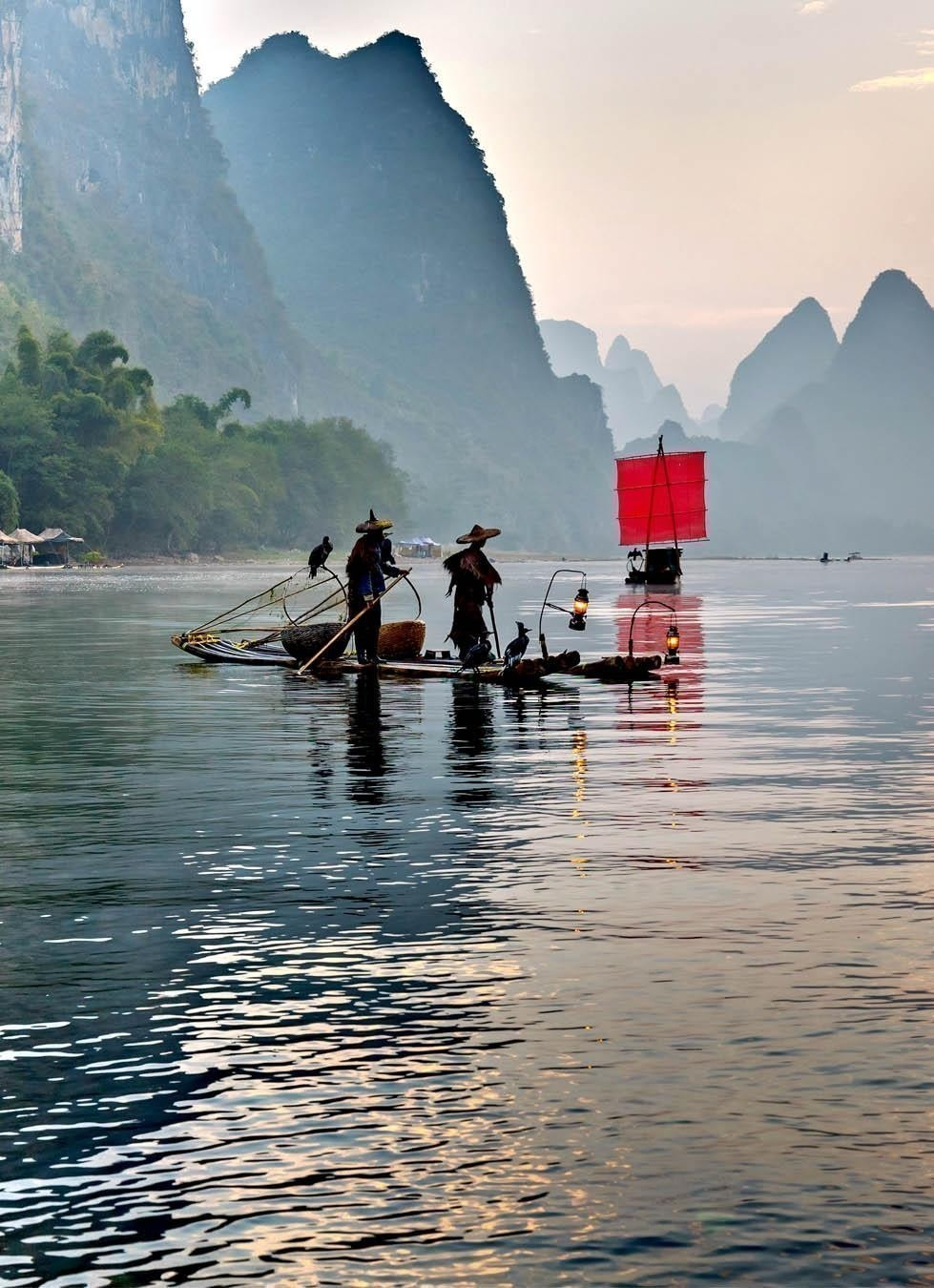 Fisherman stands on traditional bamboo boats at sunrise (boat with a red sail in the background) - The Li River, Xingping | China Travel Guide