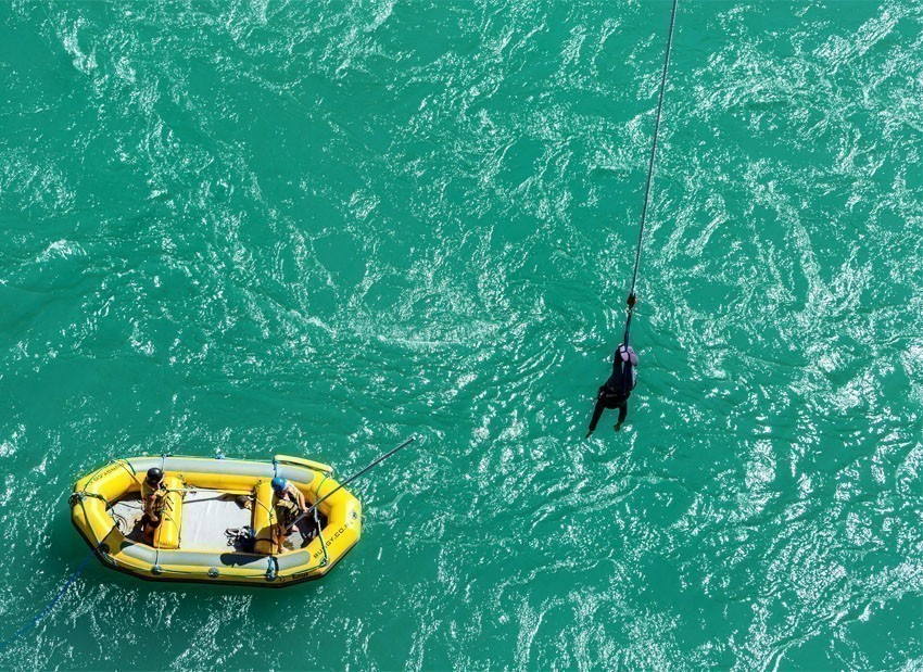 AJ Bungy's crew on rubber boat use long stick to grab their customer after bungy jump from the Kawarau Bridge in Queenstown | 7 Awesome Things to Do in New Zealand