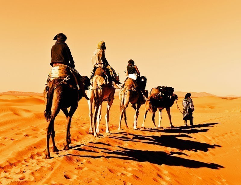 Camel caravan going through the sand dunes in the Sahara Desert, Morocco. | 10 Spectacular Places to Visit Before They Become Famous